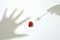 Shadow of the hand trying to take a strawberry
