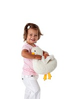 Toddler girl carrying a toy duck on white background