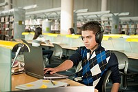 Hispanic student listening to headphones and working at laptop in library