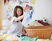 Mixed race teenage girl doing laundry on bed