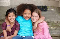 Smiling friends hugging on front stoop