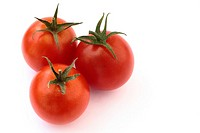 Three red tomatoes on a white background in a still life arrangement