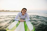 Smiling Caucasian teenage girl leaning on surfboard in ocean