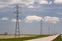 calgary, alberta, canada, metal power lines in a row running along a road with a blue sky and clouds