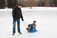 edmonton, alberta, canada, a man pulling a woman on a small sled across the ice on an outdoor rink