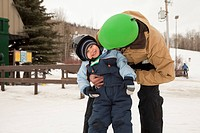 red deer, alberta, canada, a father and young son wearing helmets at a ski area