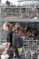 BIKES IN FRONT OF THE BIG BICYCLE PARKING LOT AT THE MAIN TRAIN STATION, AMSTERDAM, NETHERLANDS