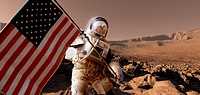 US exploration of Mars, artwork. Astronaut preparing to plant the flag of the United States of America USA on the Martian surface. Mars is a rocky des...