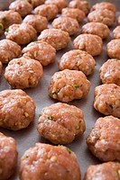 tray of raw meatballs on a baking sheet
