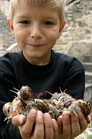 CHILD WITH A HANDFUL OF SNAILS, FRANCE