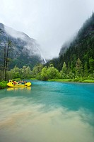 River rafting, Taku River. Rafters in an inflatable boat yellow at the confluence of Kwashona Creek blue water and the Taku River cloudy water. Bishop...