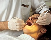 Dental examination. Dentist examining a woman´s teeth for signs of decay.