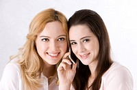 Two young women listening to one mobile phone