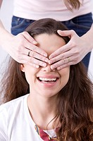Young woman covering eyes of friend