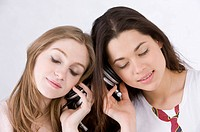Two young women sharing headphones