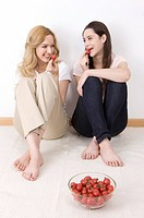 Two young women sitting together eating fruits