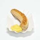 German Bratwurst, fried sausage with mustard in paper plate, close_up, elevated view