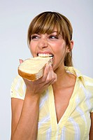 Young woman eating bread and butter