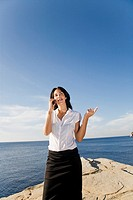 Business woman talking on the phone in a cliff in Ibiza, Balearic Islands