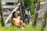 young woman sitting in meadow, leaning on wooden railings