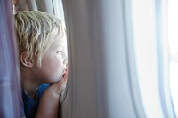 Young boy staring out plane window