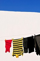 Clothes drying on clothesline and whitewashed wall