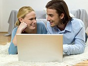 Couple lying on floor, using laptop