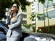 Businesswoman talking on the phone while leaning against the car