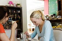 Female friends having coffee in cafe