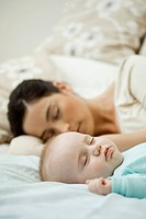 Baby napping on bed with mother