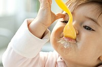 Infant eating with spoon