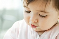 Infant with baby food on her face, portrait