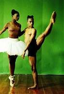 Male and female dancers stretching their legs in a studio
