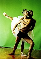 Female ballet dancer hugging a male ballet dance from back and raising her leg