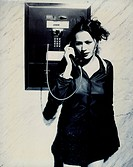 Young woman talking on a pay phone