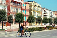 Man riding a bike in Italian resort town Sotomarina Chioggia on a street with typical Italian houses