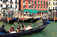 Gondolas with tourists in Venice harbor Italy