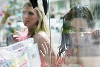 Two young women staring into window display at store