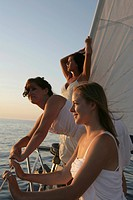 Three young woman looking at the sea from a watercraft