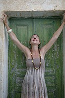 Cheerful young woman with arms out in front of a closed door
