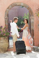 Young couple with luggage entering an archway