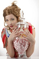 Portrait of a beautiful young woman holding a container full of candies
