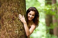 ragazza si nasconde dietro un albero