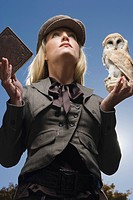 Portrait of stylish young woman with owl perched on hand and book