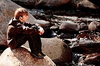 Boy sitting on stream rock listening to music                                                                                                         ...