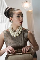 Young woman with pearls necklace looking into purse