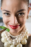 Close_up of a smiling young woman holding green pea with chopsticks