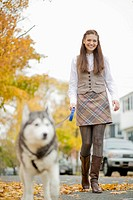 Portrait of young woman walking dog on autumn day