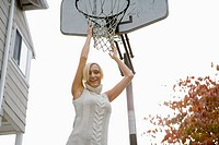 Portrait of young blonde woman hanging from basketball hoop