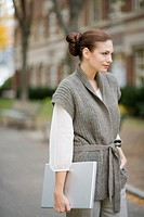Portrait of young stylish woman holding laptop on autumn day in neighborhood